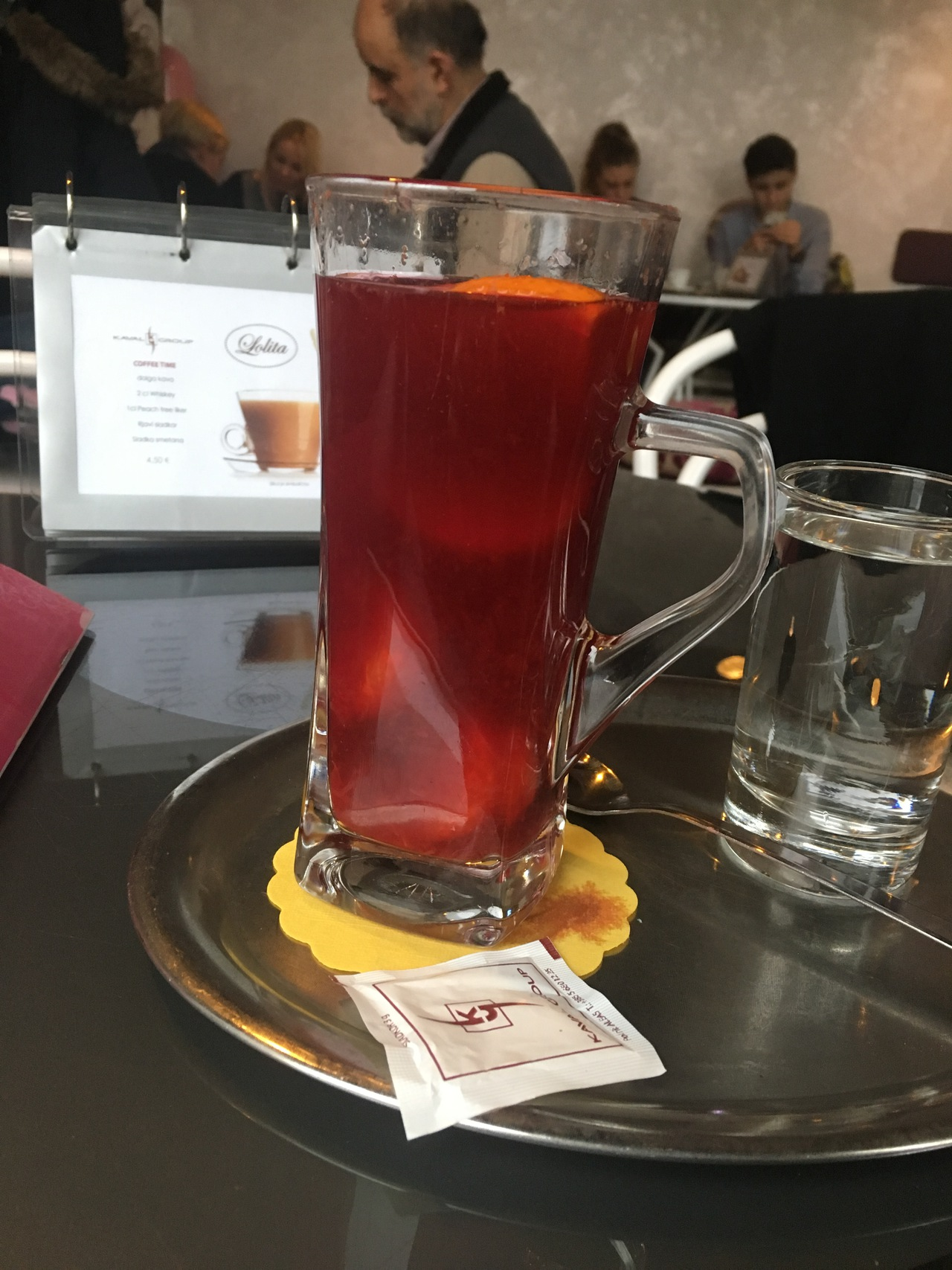 A tall glass filled with red punch. It has fruits swimming in the punch