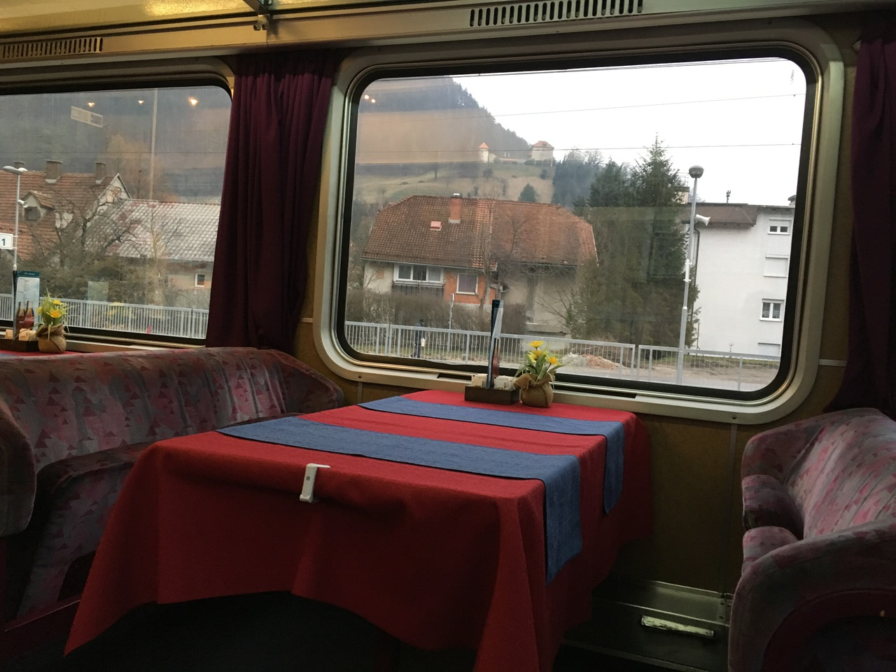 A wide open dining car with cozy benches the low backs of which offer a great view of the scenery through panorama windows